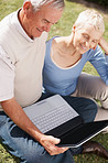Retired couple using a laptop on grass