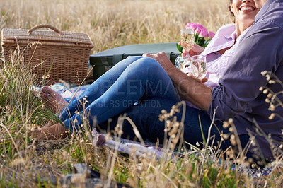 Buy stock photo Cropped image of a loving mature couple enjoying a champagne picnic together