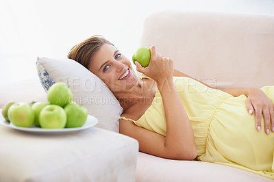 Buy stock photo A happy pregnant woman relaxing on her couch and enjoying an apple