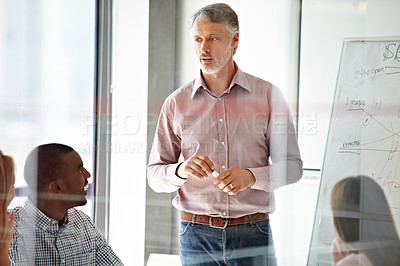 Buy stock photo Shot of a businessman presenting his ideas to his colleagues during a meeting
