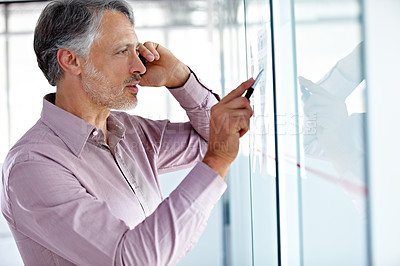 Buy stock photo A mature businessman talking on his cellphone while writing on a board
