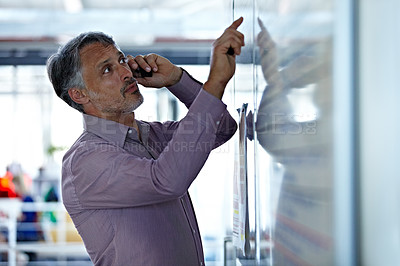 Buy stock photo A mature businessman talking on his cellphone while looking at something on the board