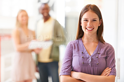 Buy stock photo Smiling young businesswoman dressed casually for work and standing with her arms folded