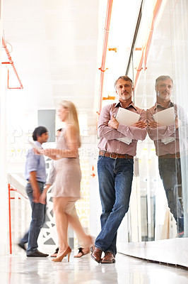 Buy stock photo Smiling mature businessman dressed casually for work and standing with his arms folded