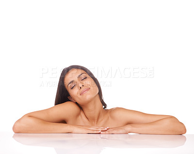 Buy stock photo Studio shot of a beautiful woman leaning on a counter against a white background