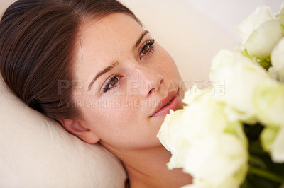 Buy stock photo A beautiful young woman lying down and holding a bouquet of white roses to her chest