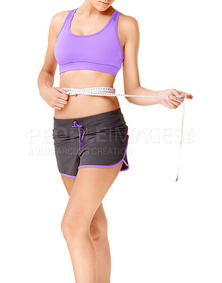 Buy stock photo Cropped shot of a slim woman in gym clothing using a tape measure to measure her waistline