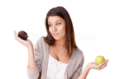 Buy stock photo A beautiful young woman choosing between an apple and a muffin