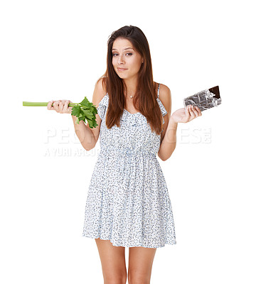 Buy stock photo A beautiful young woman deciding between a stick of celery and a slab of chocolate