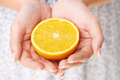 Buy stock photo Cropped image of a woman's hands holding half an orange