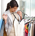 Happy woman selecting clothes whole at the mall