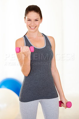 Buy stock photo Portrait of an attractive young woman in gym clothing training with dumbbells