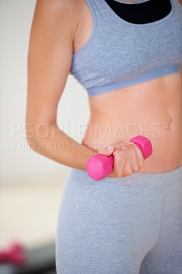Buy stock photo Cropped image of a woman's midriff while she is lifting a dumbbell at a gym