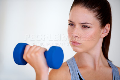 Buy stock photo An attractive young woman training with dumbbells and looking confident