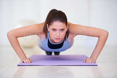 Buy stock photo Portrait of an attractive young woman doing push-ups in the gym