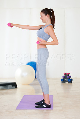 Buy stock photo Profile of a beautiful young woman training with weights