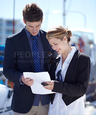 Buy stock photo Young businesspeople looking over some paperwork at the marina