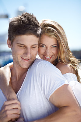 Buy stock photo Romantic young couple standing together in the sunshine at the marina