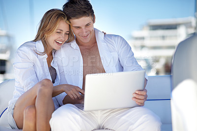 Buy stock photo Young couple using a laptop together on a yacht