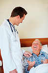 Doctor giving pills to a happy elderly man