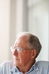 Old man wearing glasses looking away in thought