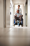 Nurse pushing an old man on a wheelchair at the corridor