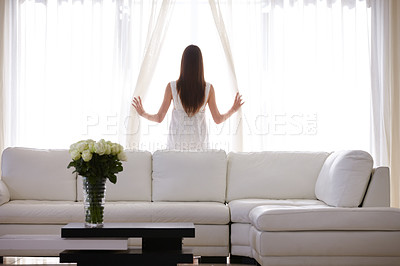 Buy stock photo A young woman looking through her living room window early in the morning