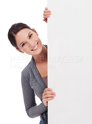 Buy stock photo Shot of a young woman looking at the camera from behind a large blank placard isolated on white