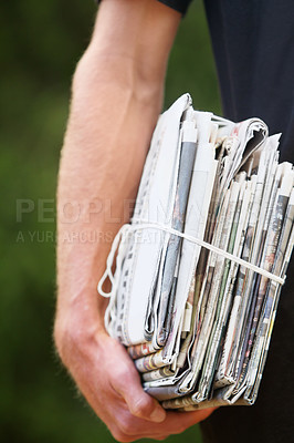 Buy stock photo Cropped shot of a man with a stack of newspaper