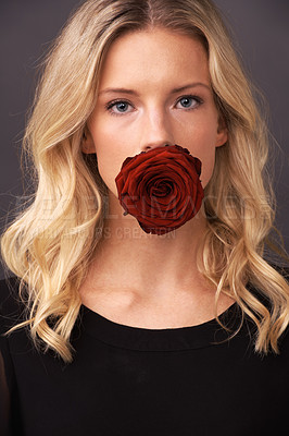 Buy stock photo Conceptual image of a blonde woman with a rose covering her mouth
