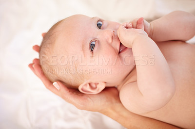 Buy stock photo Happy little baby looking up while lying in its mother's hands