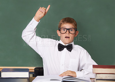 Buy stock photo A schoolboy wearing a bow-tie and glasses raising his hand to answer a question