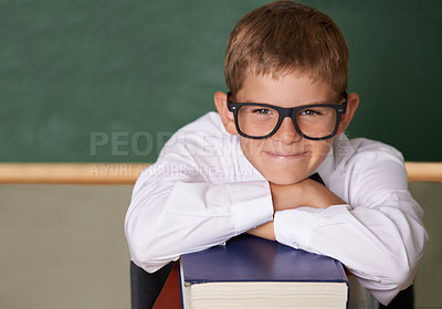 Buy stock photo A happy young schoolboy wearing glasses and a bow-tie smiling at the camera while leaning on a stack of books