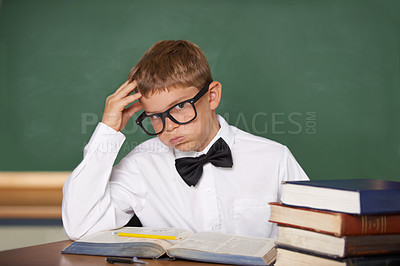 Buy stock photo A young schoolboy in glasses and a bow-tie sighing wearily while looking at the camera