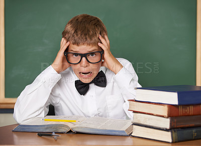 Buy stock photo A stressed-looking schoolboy in a bow-tie and glasses sitting with his hands in his hair