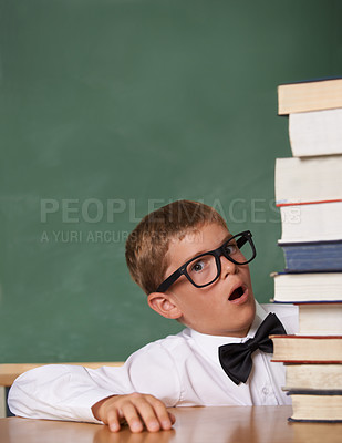 Buy stock photo A young boy wearing glasses and a bow-tie looking wearily at the camera next to a high pile of books