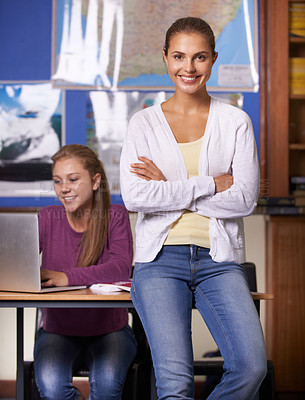 Buy stock photo A young teacher sitting on the side of her pupil's desk and smiling at the camera with her arms folded