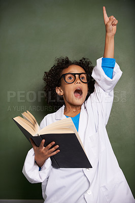 Buy stock photo An ethnic boy wearing glasses and a labcoat raising his hand to answer a question while holding a book