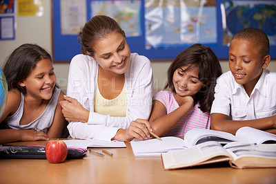 Buy stock photo A young teacher sitting with her three ethnic pupils reading through a textbook