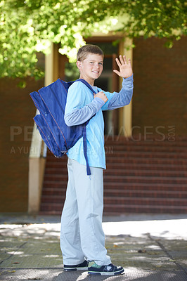 Buy stock photo A young boy wearing a backpack smiles and waves at the camera