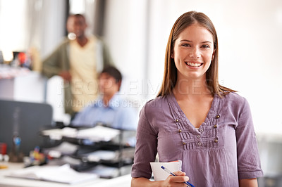 Buy stock photo Shot of a young designer holding her notepad with her colleagues in the background