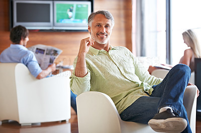 Buy stock photo A handsome businessman relaxing with colleagues in the chill room