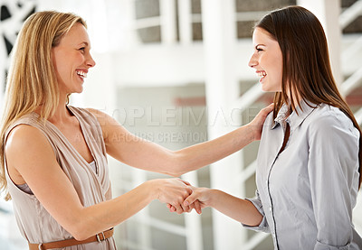 Buy stock photo Cropped shot of two attractive businesswoman laughing in the office