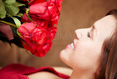 Buy stock photo An attractive young woman smelling a bouquet of roses