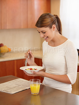 Buy stock photo An attractive young woman eating her breakfast in the kitchen