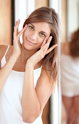 Buy stock photo An attractive young woman applying moisturizer to her face