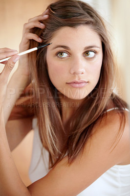 Buy stock photo An attractive young woman applying eyeliner