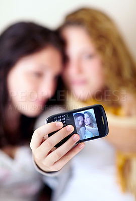 Buy stock photo Shot of two sisters taking a self-portrait with a camera phone