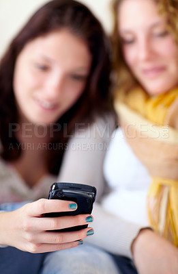 Buy stock photo Shot of two sisters reading texts on a cellphone