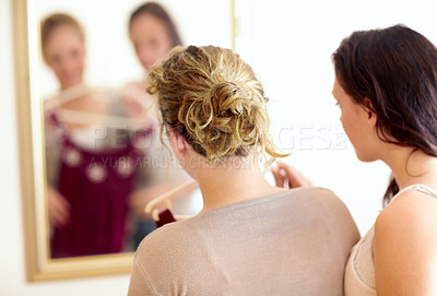 Buy stock photo Rearview shot of two sister looking at their reflection in a mirror while trying to pick some clothing